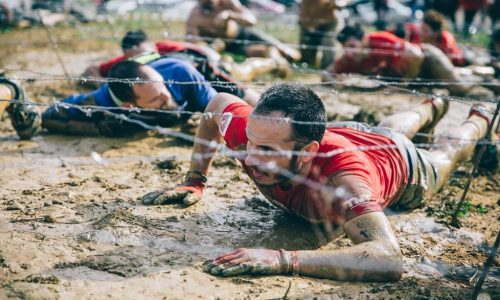 GIJON, SPAIN - JANUARY 31, 2016: The Farinato Race, a extreme obstacle race, celebrated in Gijon, Spain, on January 31, 2016. Portrait of runner crawling under a barbed wire in a test of the race.